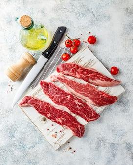 Vier stukjes rauwe biefstuk op een houten snijplank, mes, zout, peper, tomaten en olie in een fles
