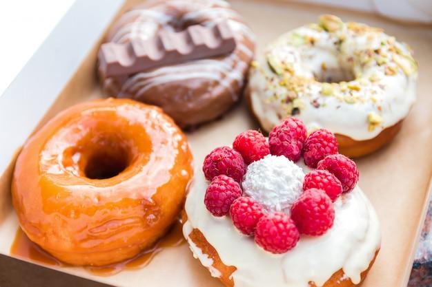 Vier stuks totaal verschillende kleurrijke en heerlijk uitziende donuts in een ecologische kartonnen doos. smakelijk fastfood-dessert