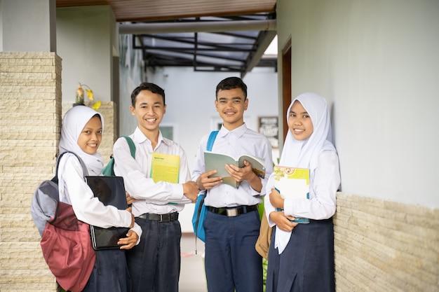 Vier tieners in middelbare schooluniformen stonden in de rij terwijl ze boeken en een laptop droegen