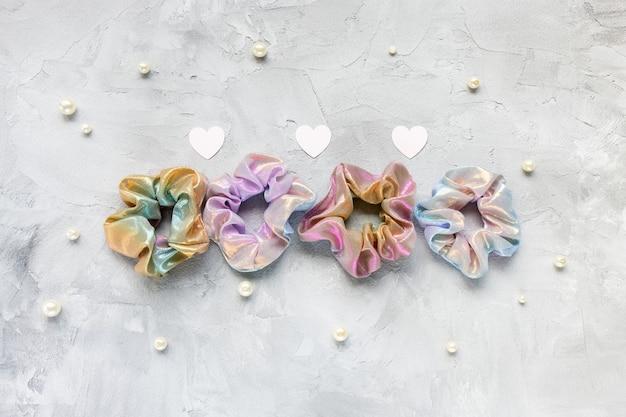 Vier trendy holografische iriserende glanzende metallic scrunchies, pastelroze papieren hartjes en witte parels op een grijze ondergrond.