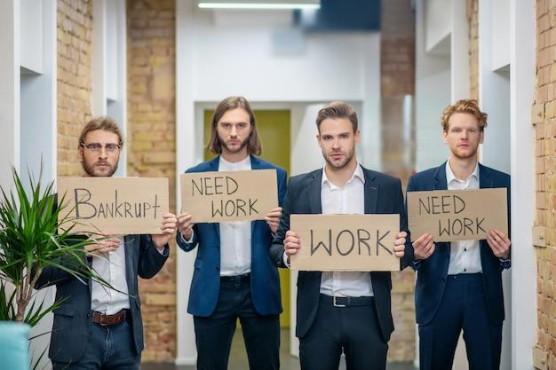 Vier trieste jonge volwassen mannen met borden in handen staan stil in de gang van het kantoor
