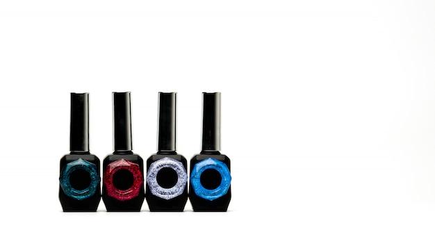 Vier unieke nagellakfles die op witte achtergrond met exemplaarruimte en leeg etiket wordt geïsoleerd, voeg enkel uw eigen tekst toe
