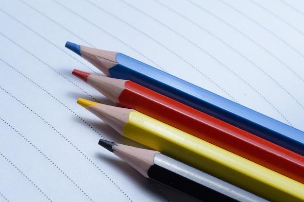 Vier veelkleurige potloden - blauw, rood, geel, zwart. liggen op een geopend notitieboekje.