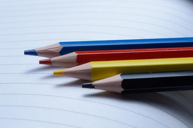 Vier veelkleurige potloden - blauw, rood, geel, zwart. op een opengeslagen notitieboekje liggen.