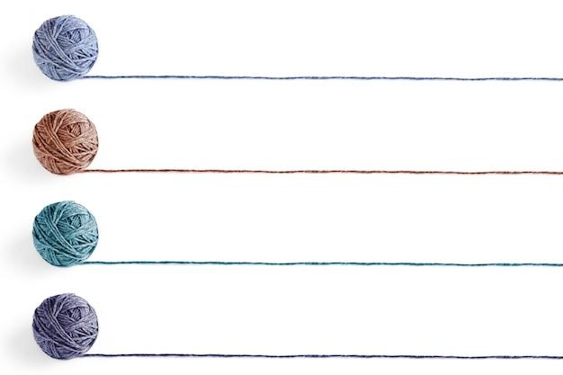 Vier veelkleurige wollen ballen van garen geïsoleerd op een witte achtergrond. leeg voor de lijst.