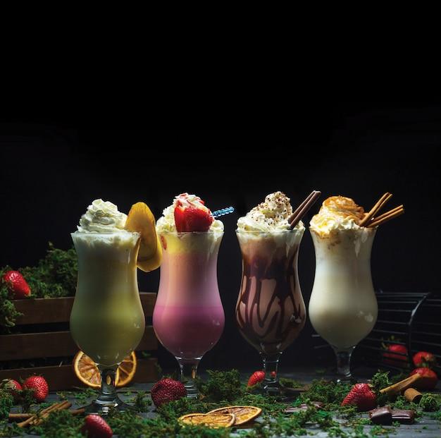 Vier verschillende cocktail smoothies met melkachtige crème bovenop