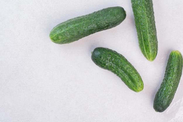 Vier verse komkommers op witte tafel.