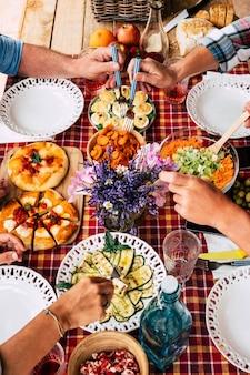 Vier volwassen mensen die samen van maaltijd genieten. rood geruit tafelkleed in de tafel buiten op het terras. houten snijplank met pizza. groenten en eieren. vers natuurlijk fruit