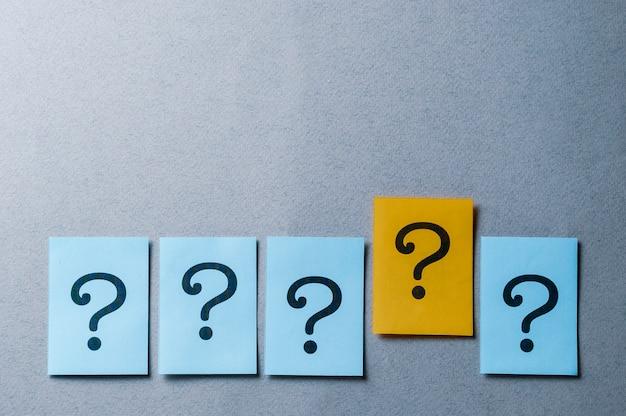 Vier vraagtekens op blauw en één op geel