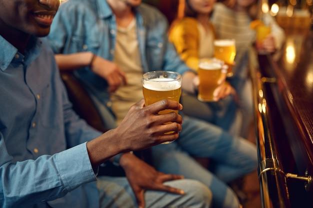 Vier vrienden drinken bier aan het loket in de bar