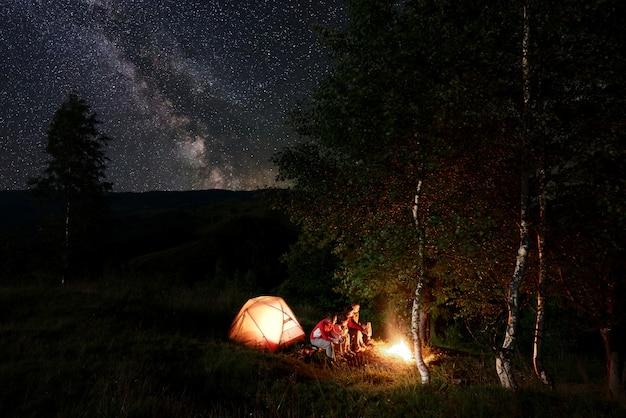 Vier vrienden toeristen rusten uit bij het kampvuur, zittend op boomstammen tijdens nacht kamperen tussen bomen in de buurt van de verlichte tent in de bergen onder ongelooflijk mooie sterrenhemel met melkweg