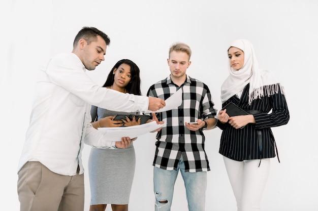 Vier vrienden van de multiculturele universiteit, mannelijke en vrouwelijke, staande op een witte achtergrond, terwijl blanke man papieren geeft om te studeren