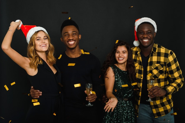 Vier vrienden van verschillende nationaliteiten gooien confetti in kerstmutsen en geweien en drinken champagne tegen een zwarte achtergrond.
