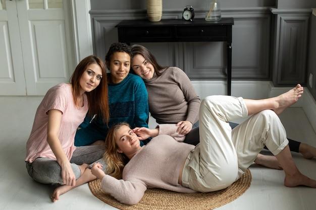 Vier vriendinnen zitten thuis op een stoel te praten. meisjes brengen thuis tijd samen door