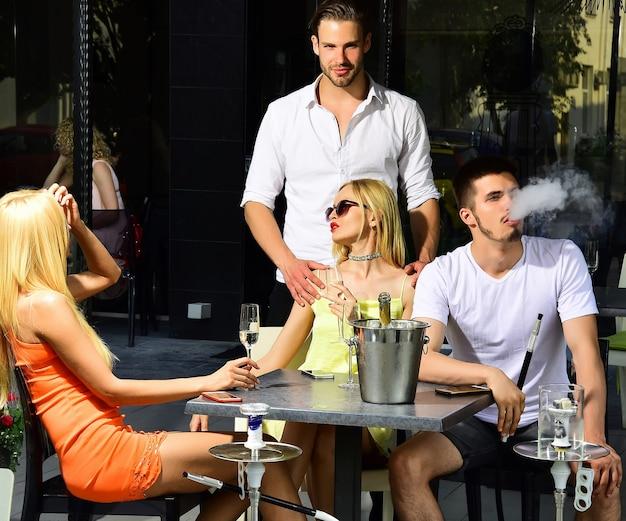 Vier vrolijke vrienden chatten tijdens de lunch in restaurant met damp waterpijp in shisha bar lounge