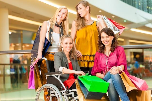 Vier vrouwelijke vrienden die in een wandelgalerij met rolstoel winkelen