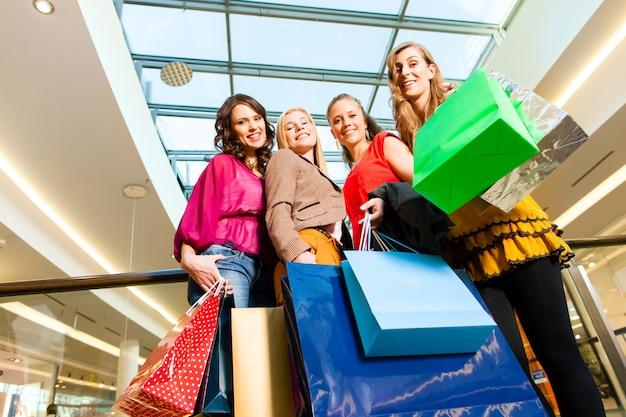 Vier vrouwenvrienden die in een wandelgalerij winkelen