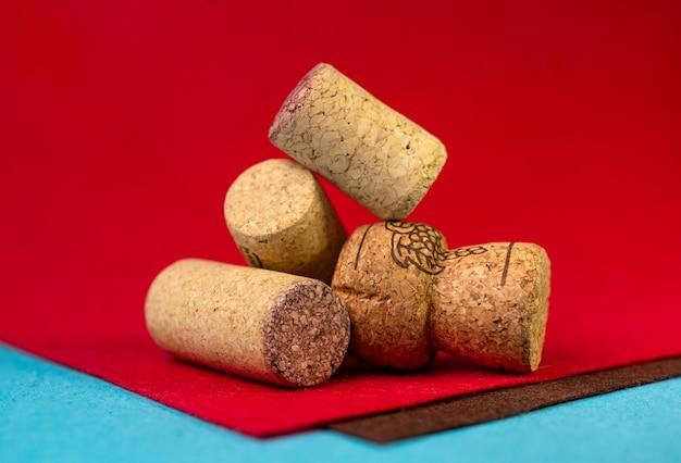 Vier wijnkurken op een rood fluwelen achtergrond.