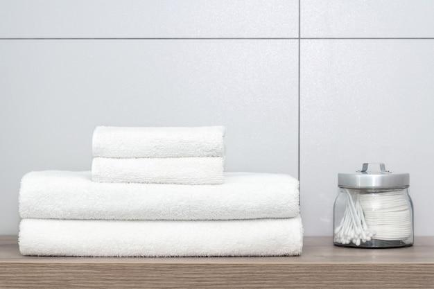 Vier witte handdoeken van verschillende grootte netjes gevouwen liggen op een houten plank en ernaast is een blik met wattenschijfjes en oorstokken tegen een keramische tegel.