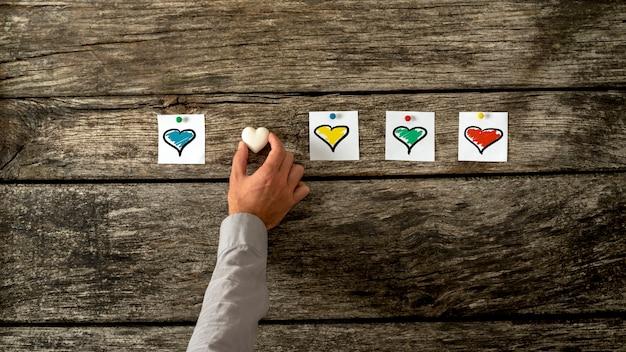Vier witte kaarten met hartjes in verschillende kleuren op een rij gespeld.