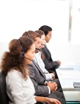 Vier zakenmensen aan de telefoon zit aan hun bureau