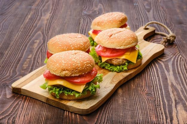 Vier zelfgemaakte hamburgers op houten serveerplank