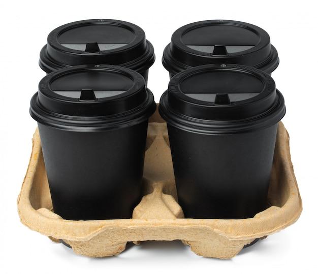 Vier zwarte meeneemkoppen van koffie in een dienblad op witte achtergrond