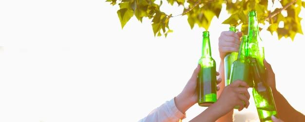 Vieren. handen van vrienden, collega's tijdens bier drinken, plezier maken, rammelende flessen, glazen samen.