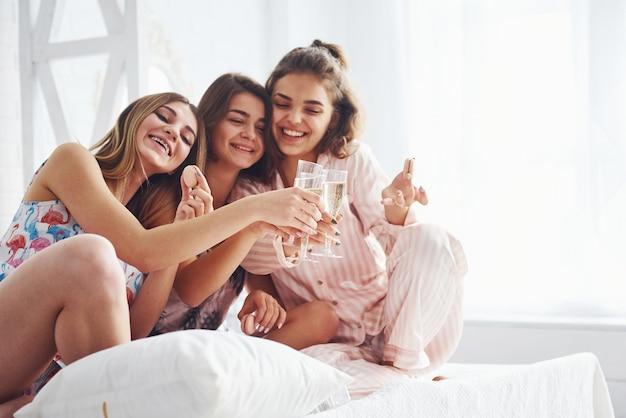 Vieren met glazen alcohol in handen. gelukkige vrouwelijke vrienden die plezier hebben op een pyjamafeestje in de slaapkamer.