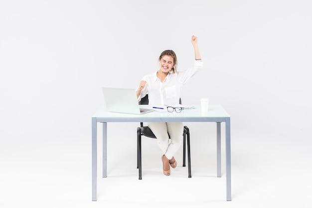 Vierende onderneemster bij bureau met laptop die op witte achtergrond wordt geïsoleerd