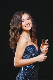 Vierende vrouw. vakantiemensen. mooi meisje met perfecte make-up bedrijf glas champagne