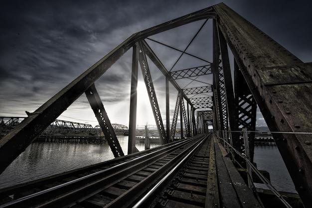 Vierendeelbrug met treinspoor bij het meer en de adembenemende zon schijnt in de donkere lucht
