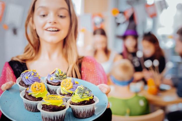 Viering cupcakes. mooi blonde-haired meisje die gelukkig met plaat met viering cupcakes voelen ter gelegenheid van verjaardag