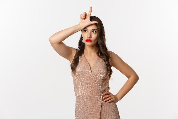 Viering en feestconcept. aantrekkelijke jonge vrouw met rode lippen, glamour jurk, verliezer teken op voorhoofd tonen en wegkijken onwetend, staande op witte achtergrond.