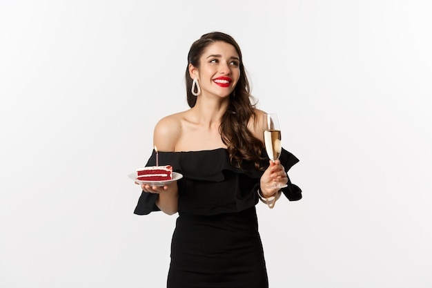 Viering en feestconcept. modieuze vrouw met verjaardagstaart met kaars en champagne drinken, glimlachend en op zoek opzij, staande op witte achtergrond.