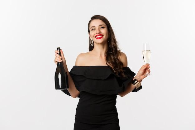 Viering en feestconcept. stijlvolle brunette vrouw in glamour jurk met fles en glas champagne, glimlachend tevreden, staande op witte achtergrond.
