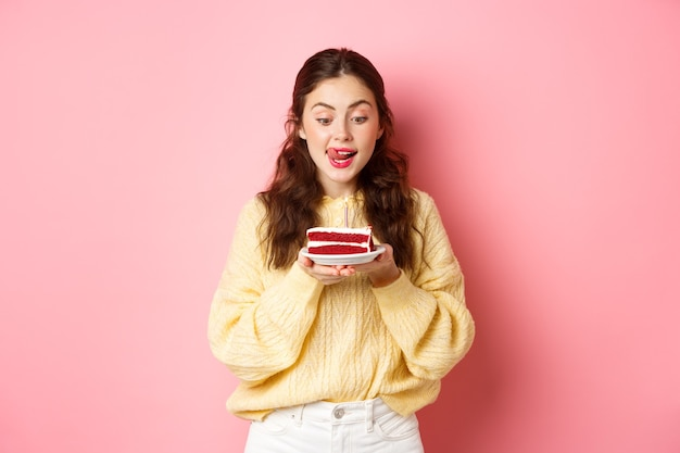 Viering en feestdagen. fijne verjaardag meisje likt haar lippen en kijkt met verleid gezicht naar verjaardagstaart, wil bijten, staand tegen roze muur.