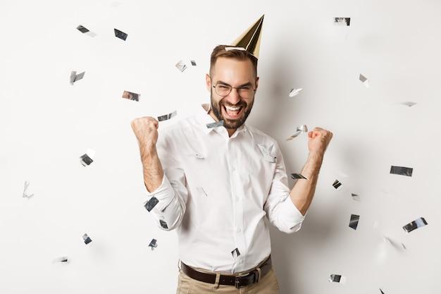 Viering en feestdagen. gelukkig man dansen op verjaardagsfeestje met confetti, b-day hoed dragen en vreugde, staande op witte achtergrond.