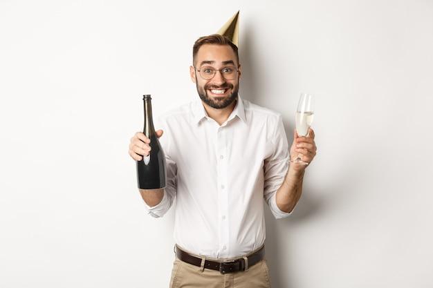 Viering en feestdagen. gelukkige verjaardag man genieten van b-dag feest, grappige kegel hoed dragen en champagne, witte achtergrond drinken.