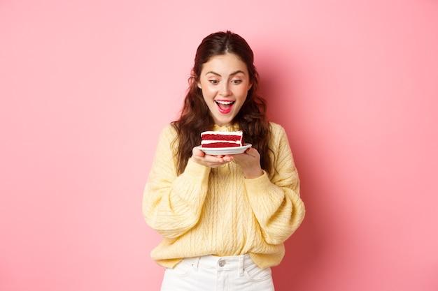 Viering en feestdagen gelukkige verjaardag meisje staart naar heerlijk verjaardagstaart dessert en glimlacht staat tegen roze muur