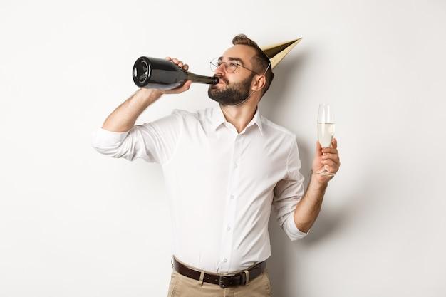 Viering en feestdagen. man chamapgne drinken uit fles op verjaardagsfeestje, staande tegen een witte achtergrond.