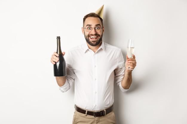Viering en feestdagen. opgewonden man genieten van verjaardagsfeestje, b-day hoed dragen en champagne drinken, staande op witte achtergrond.