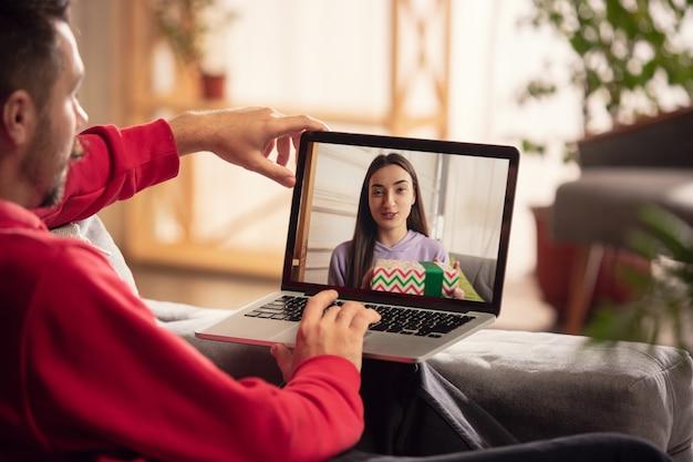 Viering en feestdagen tijdens quarantaineconcept. vrienden of familie die cadeaus uitpakken terwijl ze praten via een videogesprek. zie er gelukkig, opgewekt en oprecht uit. concept van nieuwjaar, technologieën, emoties.