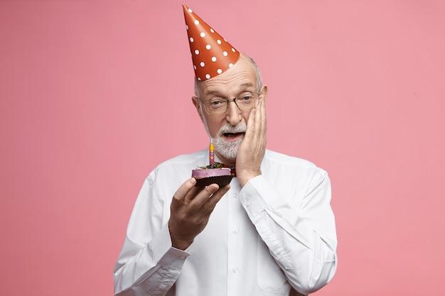 Viering en jubileum concept. emotionele senior man met dikke grijze baard gekleed in mooie elegante kleding, verjaardagstaart vasthouden en gezicht in shock aanraken, verbluft met verrassingsfeest