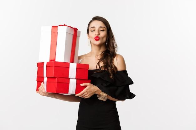 Viering en kerstvakantie concept. domme vrouw in elegante zwarte jurk, met kerst- en nieuwjaarscadeaus, tuit lippen voor kus, permanent blij op witte achtergrond.