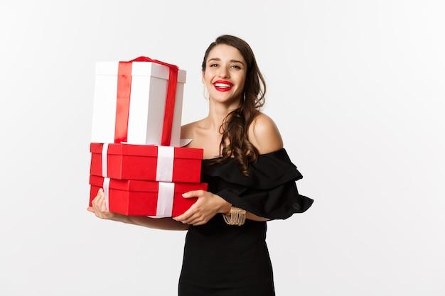 Viering en kerstvakantie concept. modieuze vrouw in zwarte elegante jurk, houdt cadeautjes en glimlacht, staande op een witte achtergrond.