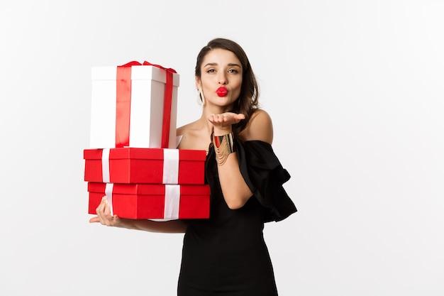 Viering en kerstvakantie concept. mooie vrouw in elegante zwarte jurk die cadeautjes vasthoudt, luchtkus verzendt naar de camera, staande op een witte achtergrond.