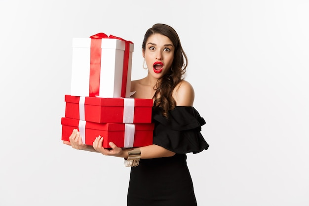 Viering en kerstvakantie concept. mooie vrouw in zwarte jurk die geschenken vasthoudt en verrast kijkt, staande op een witte achtergrond.