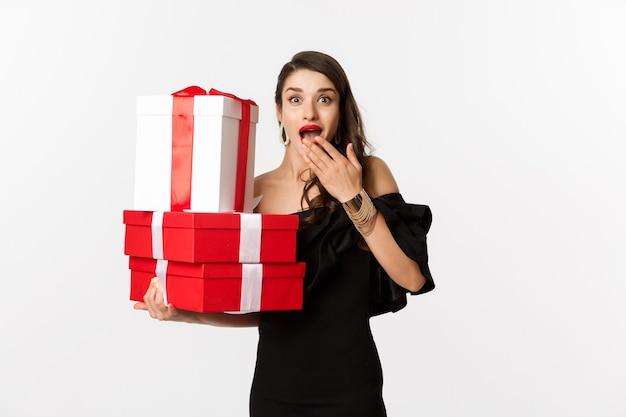 Viering en kerstvakantie concept. vrouw die kerstcadeaus vasthoudt en er verrast uitziet, cadeautjes ontvangt, staande op een witte achtergrond.