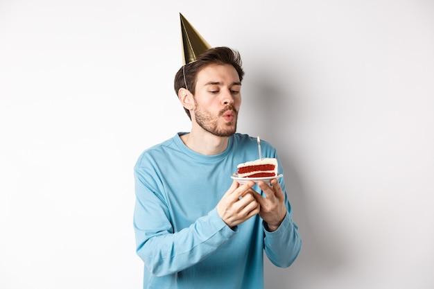 Viering en vakantie concept. gelukkig dwaze kerel blaast kaars op de taart en het maken van wens, staande in feestmuts op witte achtergrond.